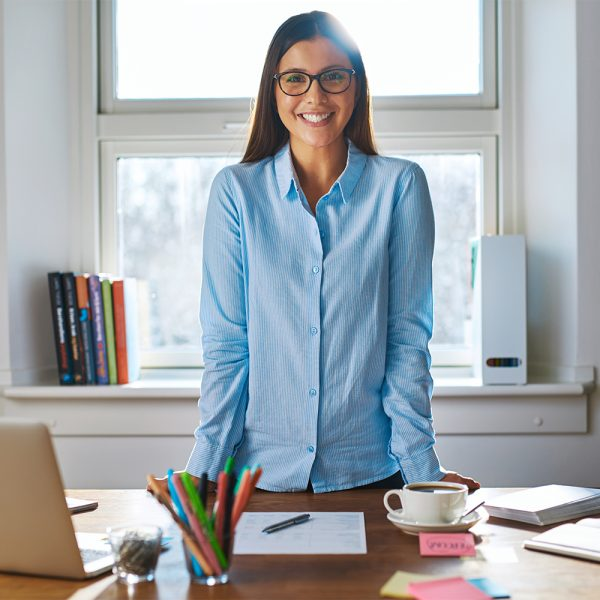 Woman standing at desk Broker Policy Administration